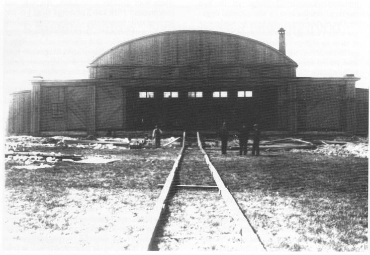 Fabrikkhallen sett fra sjøen, bilde tatt av fotograf Larsen tidlig i 20-årene. Den primitive jernbanen kunne frakte fly opp og ned mellom fabrikken og sjøen.