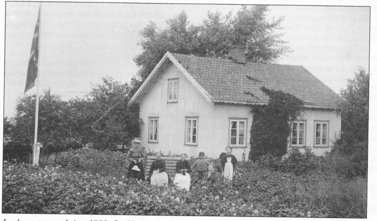 Jordmorstua omkring 1900. Strikkende dame (nr. 3 fra venstre) er Elisabeth Marie Sørensen (mormor til nåværende eier Karl Gjersøe), stående gutt er Søren Sjulsen, i gresset hans mor Marie Gurine Sørensen (datter av Elisabeth Marie) og til høyre Elisabeth Gjersøe (også datter til Elisabeth Marie) og mor til Karl Gjersøe.