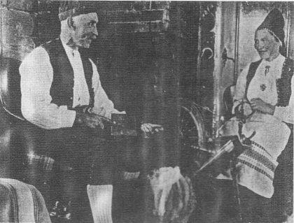 """Anders og Marie Varpe med karde og rokk. Bildet er tatt i """"Tussestua"""" - ei hytte som Anders Varpe bygde på Føynland i 1937. Foto: Sunnfjord Museum."""