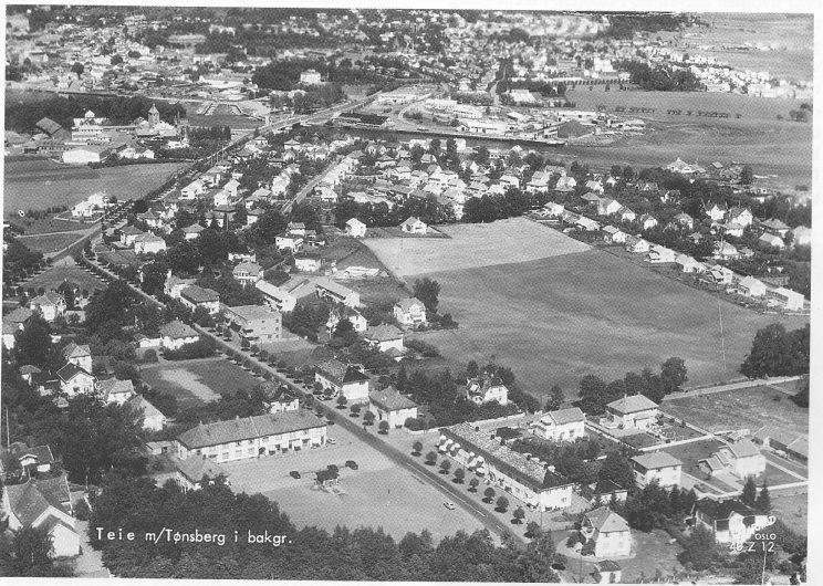 Luftfoto av Teie med Tønsberg i bakgrunnen. Menighetshuset nederst i venstre bildehjørne. Foto: K Harstad Kunstforlag.