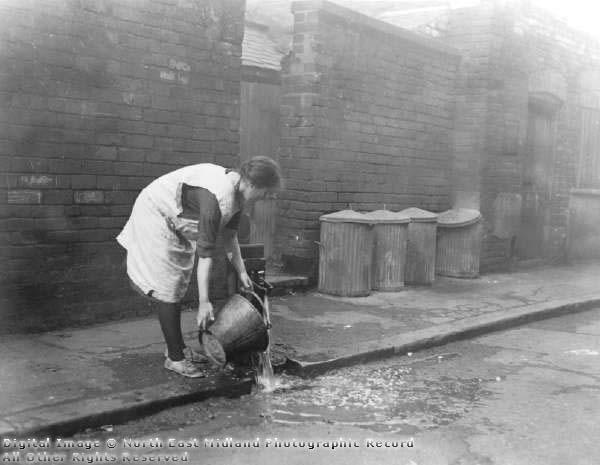 Kvinna hämtar vatten vid vägen, med soptunnor i bakgrunden längs väggen.