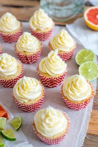 Paloma cupcakes frosted and lined up, with grapefruit and lime wedges and a bottle of tequila in the background.