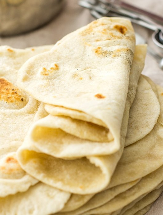 A stack of three soft flour tortillas folded on top of one another.
