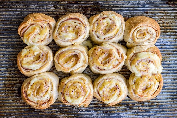 A baking sheet loaded with turkey gouda rolls ready for a party.