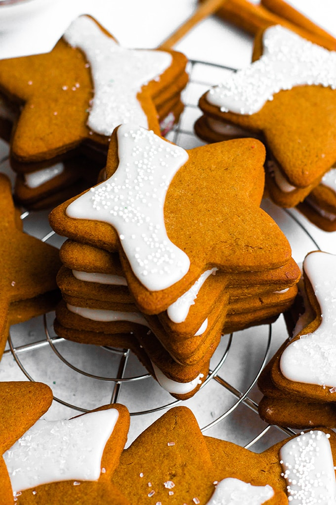 Close-up image of gingerbread cookies cut into a simple five-point star shape, with a pretty crescent of shiny white frosting and sprinkles.