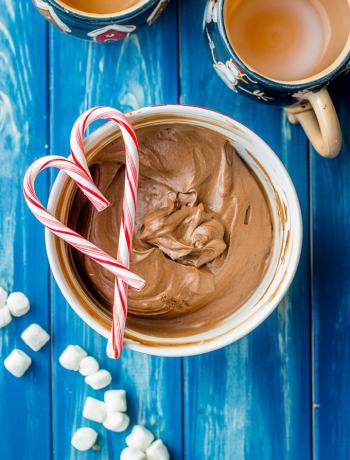 A bowl full of classic hot cocoa mix, layered with peppermint candy canes in a heart shape.