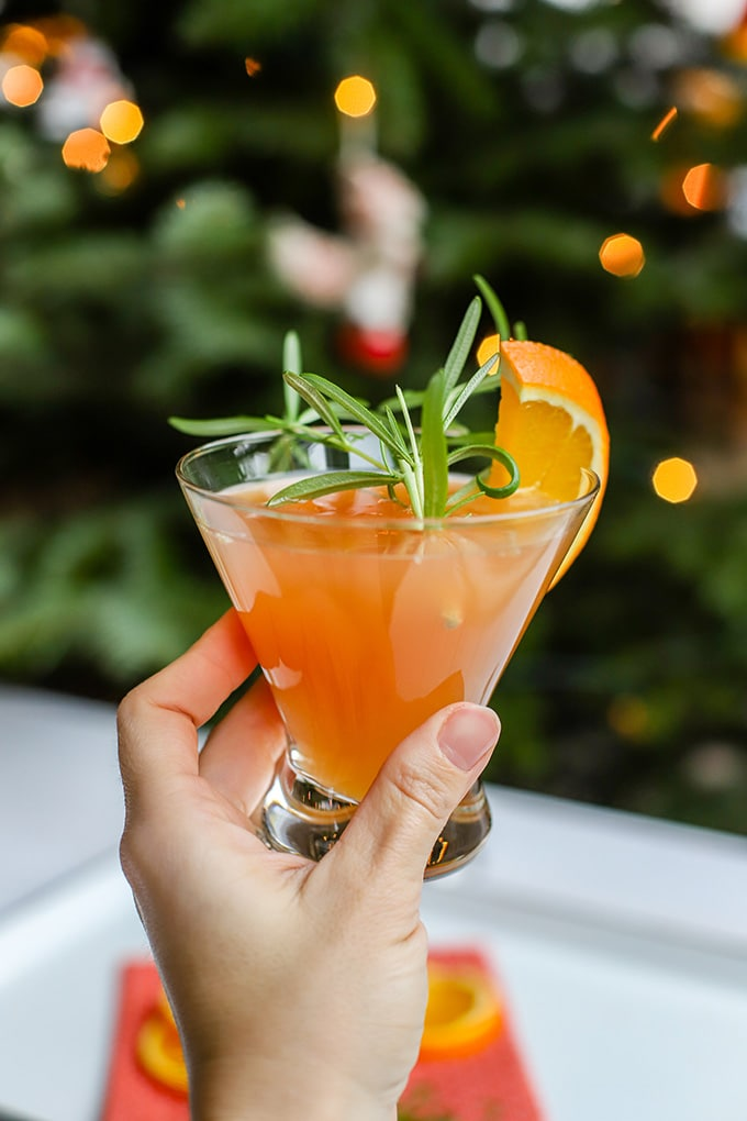 A hand holding up an orange pomegranate Prosecco cocktail in front of a Christmas tree.