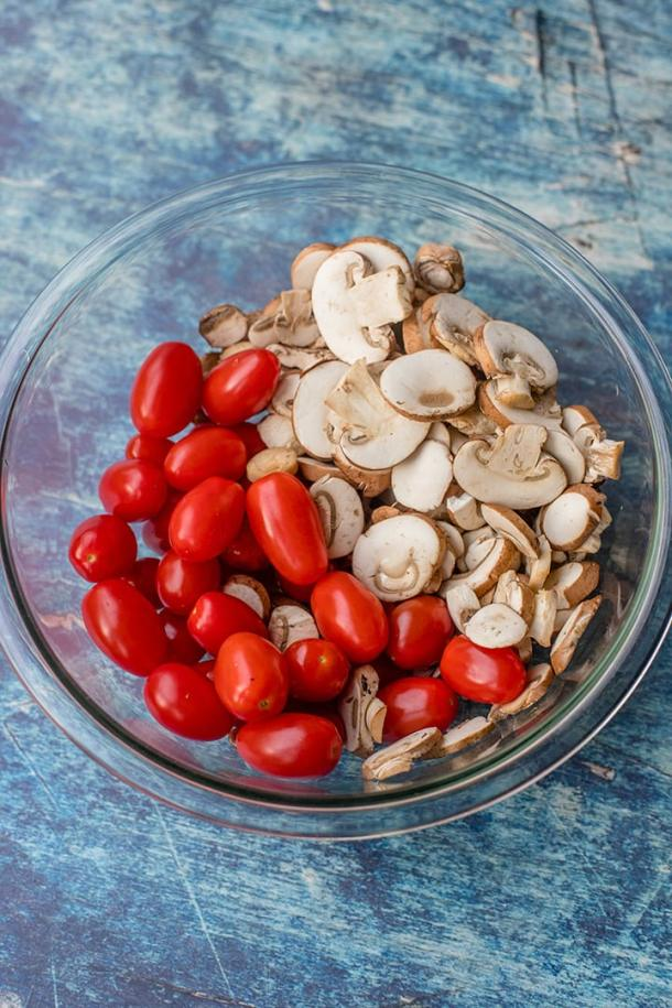 Cherry tomatoes and sliced white mushrooms in a large prep bowl.