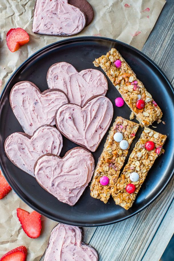 A plate of strawberry-frosted chocolate sugar cookies plus M&M granola bars, perfect for gifting.