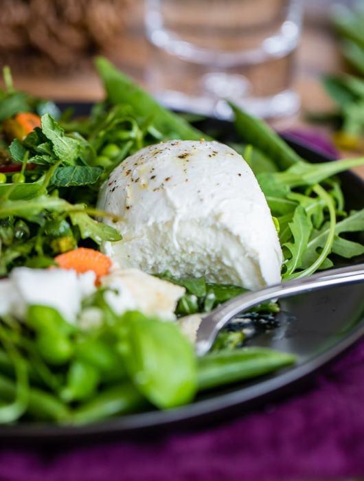 Close-up of a cut-open ball of fresh Buffalo mozzarella cheese nestled in a bright salad of arugula and sugar snap peas.
