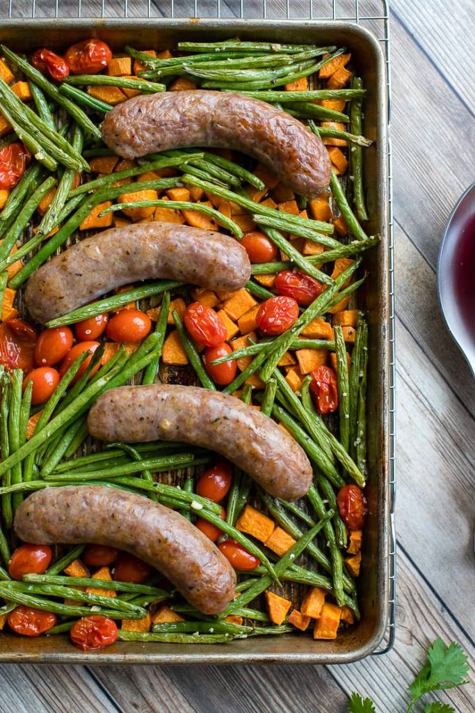 A pan filled with an Italian sausage sheet pan dinner with roasted sweet potatoes, green beans, and cherry tomatoes, fresh out of the oven and ready to serve.