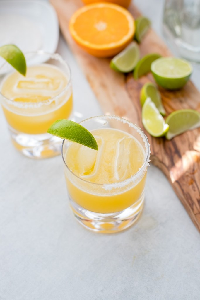 Two cocktail glasses filled with skinny margaritas and garnished with fresh lime.