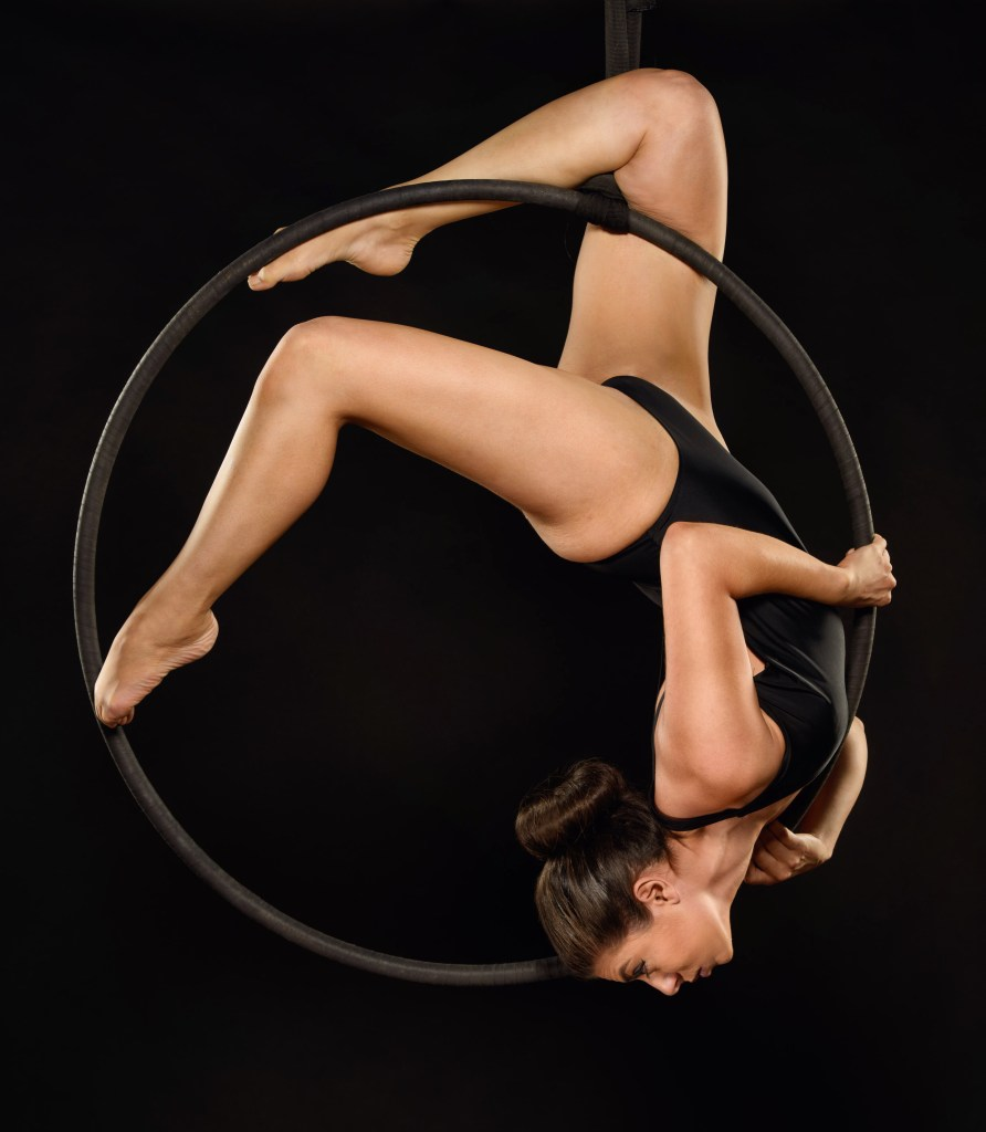 Graphic Designer Eman strikes an inverted pose in an aerial hoop.
