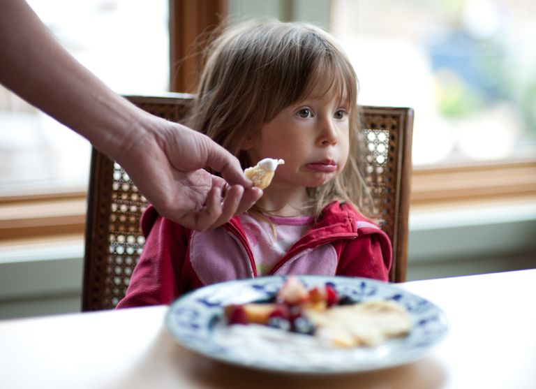 Little girl making a face and refusing the food in front of her