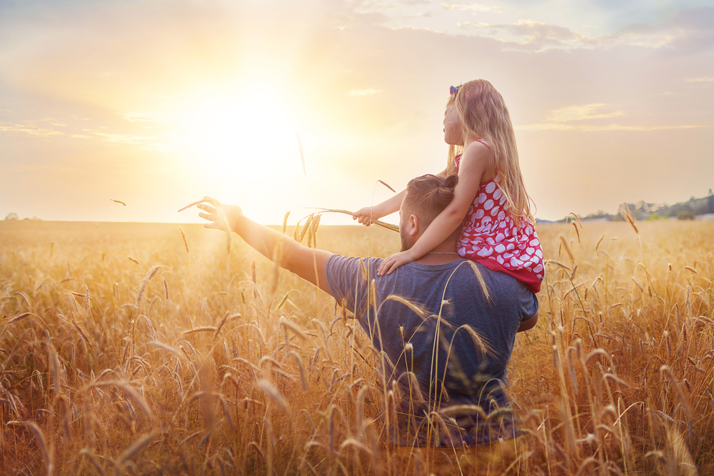 A farmer pointing at the sunset with his daughter on his shoulders in a field of wheat