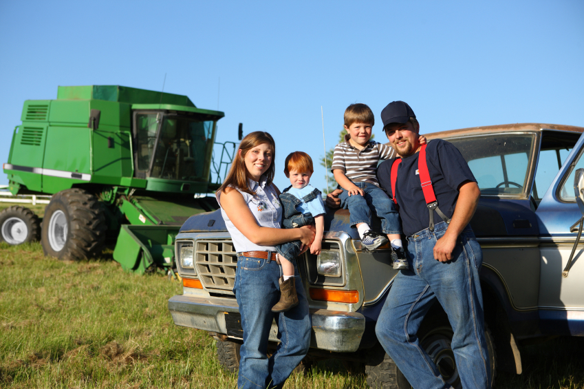 A family of farmers posed with a pickup and a combine.