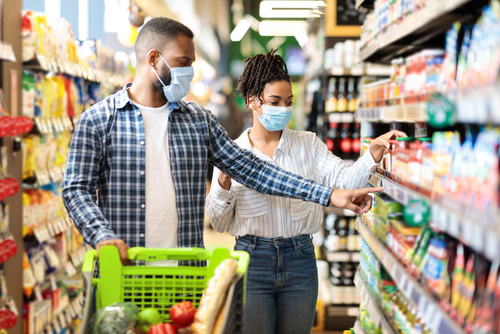 couple in masks grocery shopping