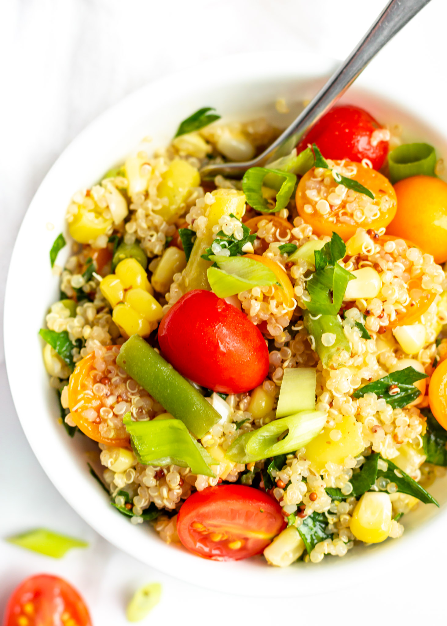 A Summery Vegan Quinoa Salad recipe perfect for lunch every day of the week. This easy summer-inspired salad is made with fresh vegetables, like green beans, corn and tomatoes, and a simple sweet Dijon dressing that is delicious served warm or cold. Give this clean eating, meal prep recipe a try!