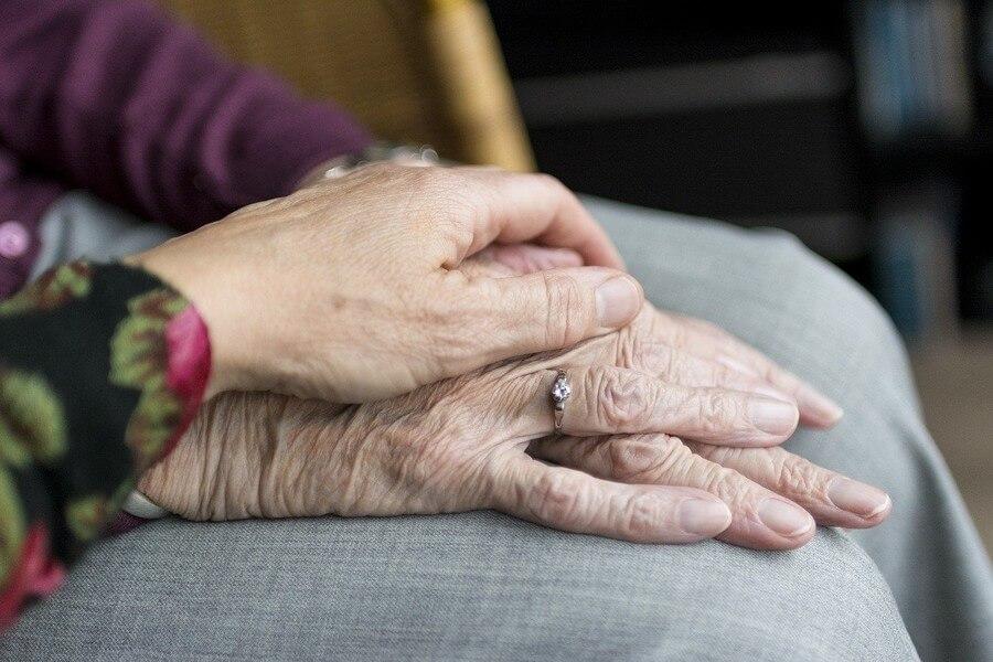 une main jeune sur une main de femme âgée