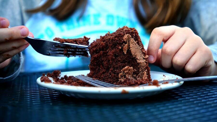 filette qui mange une part de gâteau au chocolat