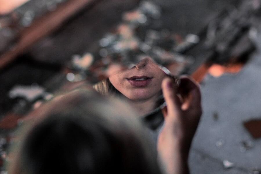 femme qui se regarde dans un miroir brisé