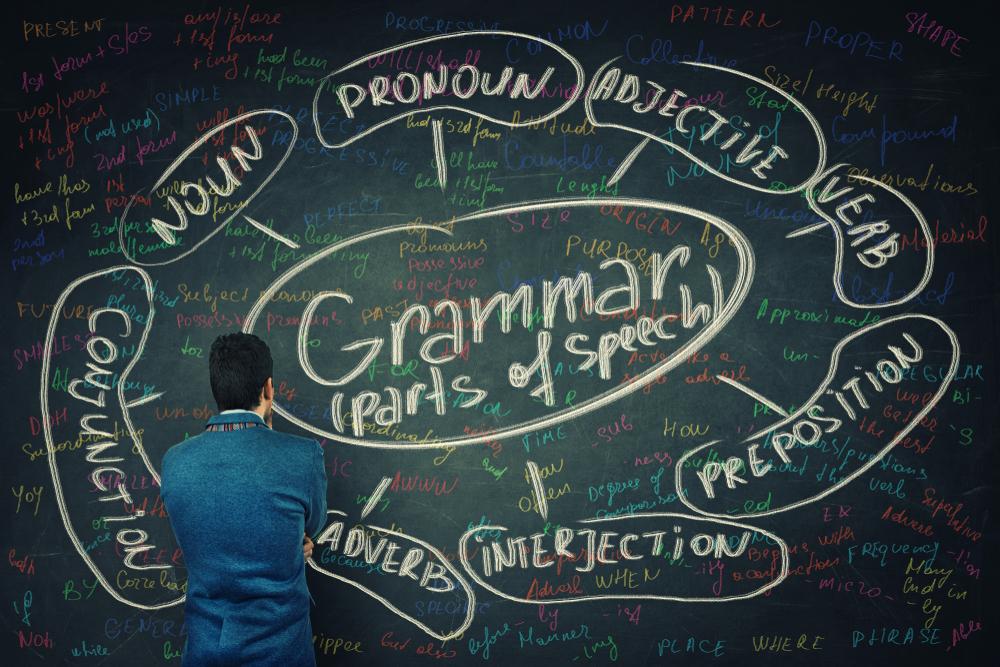 mężczyzna przy tablicy z gramatyką