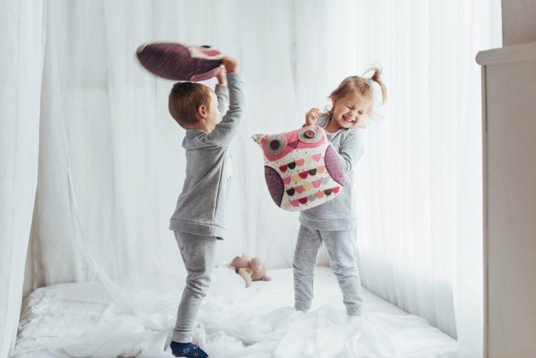 dzieci bawiące się w bitwę na poduszki