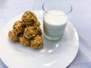 Energy balls stacked on a white plate next to a glass of milk