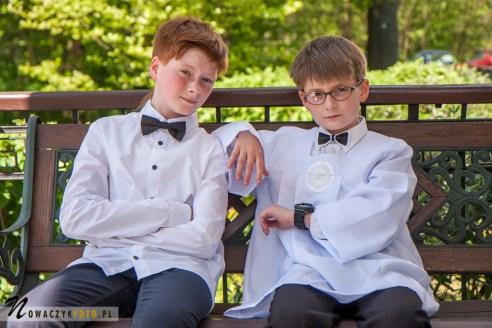Zdjęcie dwóch chłopców w strojach komunijnych siedzących na ławce pod kościołem