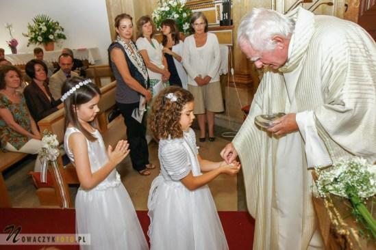 Zdjęcia komunijne dziewczynek w kościele idących po opłatek