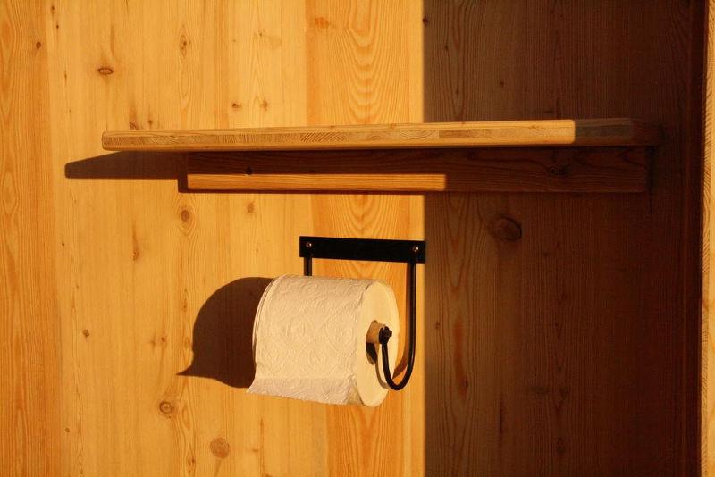 Toilettenhaeuschen Wald. Standard Ausstattung Toilettenpapierhalter und Ablagebrett