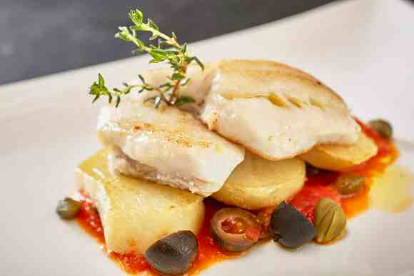 PAN-FRIED SEA BASS FILLET WITH ROASTED POTATOES, CAPERS AND CHERRY-TOMATO SAUCE