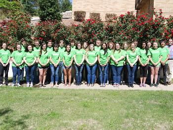 Group shot of teen-aged volunteers posing outside building