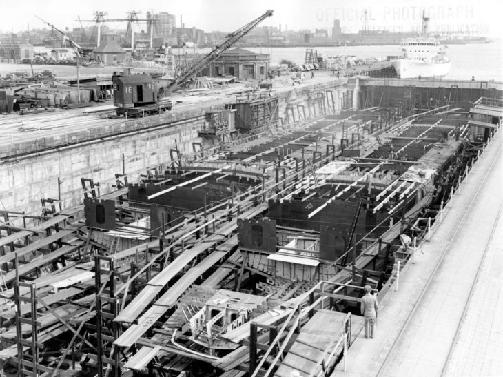 Photograph with hulls and scaffolding in a dry dock. Crane and industrial equipment in background.