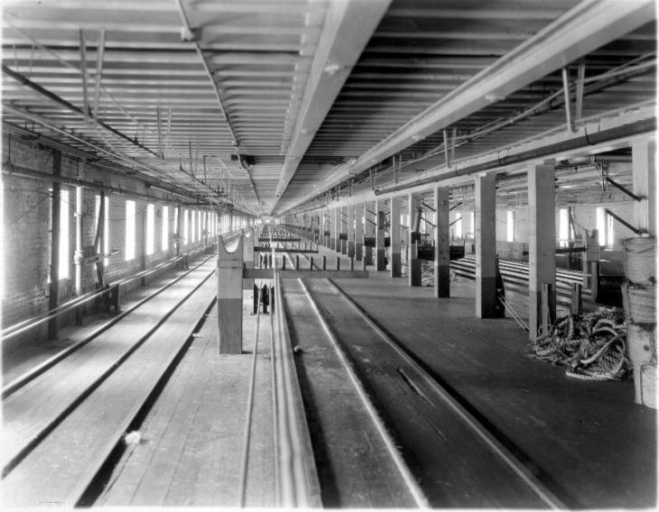 Long, empty room with tracks on the floor, pillars and rope piled in corner