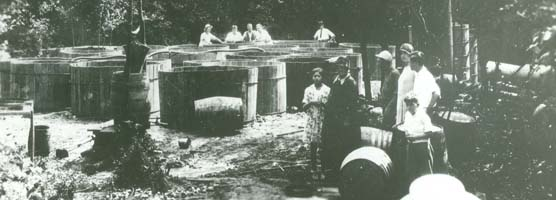 A group of people standing around large wooden vats.