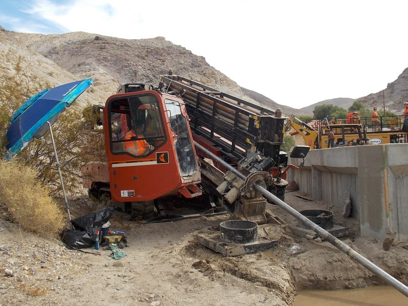 A blue umbrella is set up on the left. In the image center is an orange drill rig with a person sitting in it. The drill is going at a diagonal angle into what appears to be a mud puddle. A concrete-walled reservoir is on right in background.