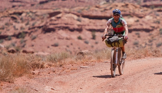 A smiling man with cycling gear rides a mountain bike on a dirt road in the desert