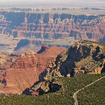 ön planda ağaçlarla kaplı bir plato, sağda ormanın içinden ve kanyonun kenarı boyunca iki şeritli bir otoyol.  Manzara, uzaktaki dik kayalıkların altında Colorado Nehri ile kanyon zirveleri ve oluşumlarının bir görüntüsüne açılıyor.