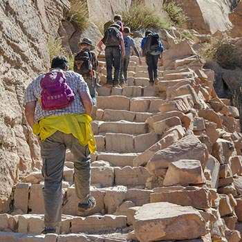 birkaç çocuğu olan bir aile taş merdivenlerden yapılmış dik bir patikaya tırmanıyor