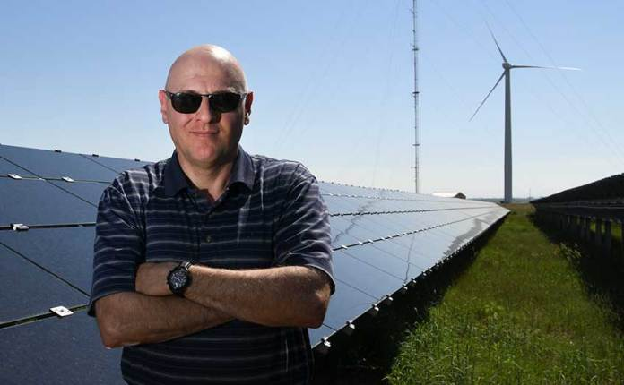 An engineer in front of solar panels and a wind turbine.