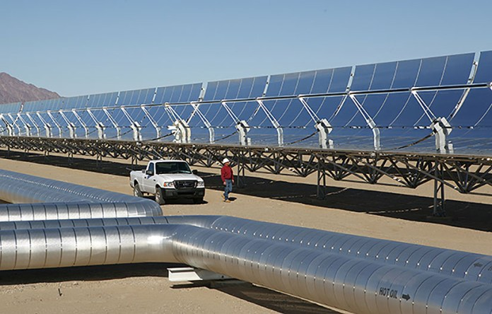 Photo of concentrated solar power parabolic trough receivers in a desert environment