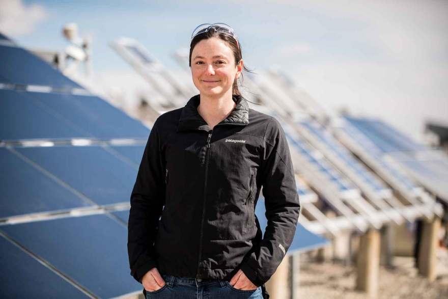 A pesquisadora da NREL, Adele Tamboli, co-autora de um artigo recente sobre células fotovoltaicas baseadas em silício, está em frente a uma série de painéis solares. Crédito: Dennis Schroeder
