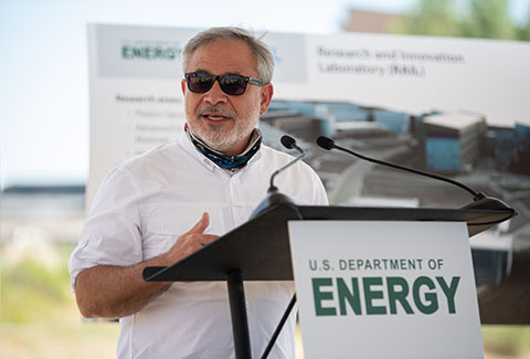 A man speaking at a podium labeled with Department of Energy