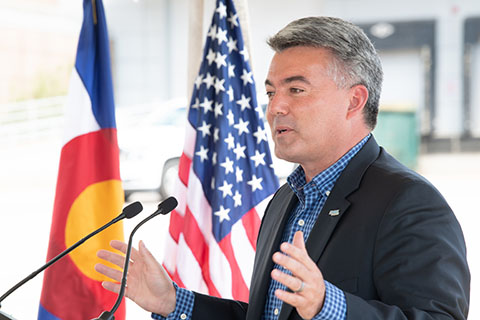 A man speaking at a podium with the U.S. flag and the Colorado flag in the background