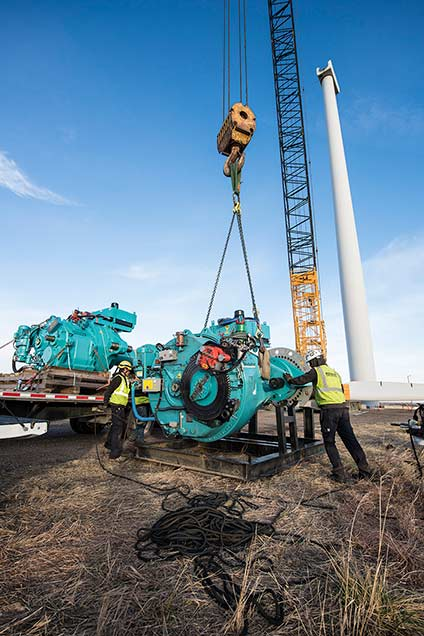 A crane lifts lowers a wind turbine gearbox onto a wooden pallet.