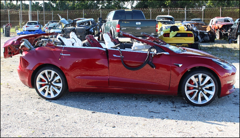 Photo of Tesla Model 3 with extensive roof damage photographed postcrash at tow yard.