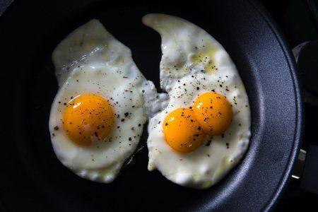 three sunny side up eggs on black ceramic plate