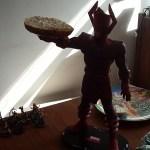 A large plastic super villain figure holds a bagel.