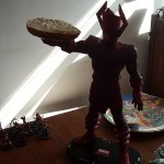 A large plastic super villain figure holds a bagel.